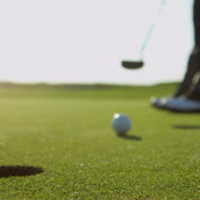 stock-footage-close-up-legs-feet-male-professional-golfer-using-putter-to-hole-the-ball-slow-motion-shot-on-red